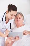 Doktor och patient som ser den digitala minnestavlan Fotografering för Bildbyråer