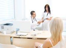Doktor och sjuksköterska som talar till tålmodign Fotografering för Bildbyråer