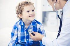 Doktor och t?lmodigt barn Unders?kande pys f?r l?kare Vanligt medicinskt bes?k i klinik care h?lsomedicinen fotografering för bildbyråer