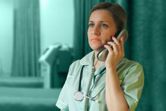 Doktor- oder Krankenschwesteranruf telefonisch Frau in der Uniform mit Hörer und im Stethoskop um Hals spricht stockbilder