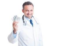 Doktor oder Mediziner, die Pillentabletten halten und zeigen Stockbilder