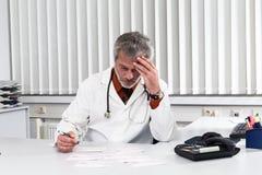 Doktor overstressed på hans kontorsskrivbord Arkivfoto