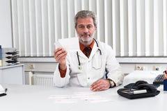 Doktor overstressed på hans kontorsskrivbord Royaltyfria Bilder