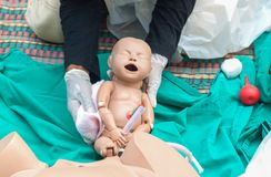 Doktor person med paramedicinsk utbildning, refresherutbildning som hjälper barnsbörden som är nyfödd med den medicinska attrappe Arkivfoto