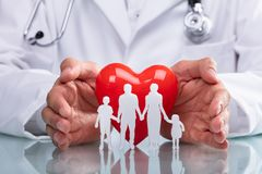 Doktor Protecting Red Heart mit Familien-Zahl stockfoto