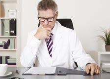 Doktor Reading Medical Results på kontoret Arkivbild