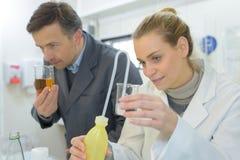 Doktor riecht Flüssigkeit während behilfliches Schauen stockbild