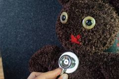 Doktor ` s Hand, die Stethoskop hält, setzte an nette braune handgemachte Grippe lizenzfreie stockfotografie