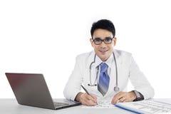 Doktor schreibt eine Verordnung und das Betrachten der Kamera Lizenzfreies Stockbild