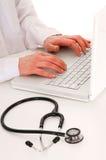 Doktor am Schreibtisch mit Stethoskop Lizenzfreies Stockbild