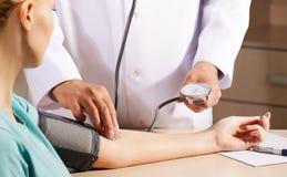 Doktor in seinem messenden Blutdruck des Büros Lizenzfreie Stockfotografie