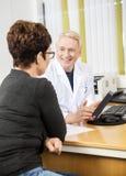 Doktor Showing Digital Tablet till den kvinnliga patienten arkivfoton