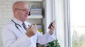 Doktor Smile och samtal med en patient på Smartphone att använda som Hand-är fritt lager videofilmer