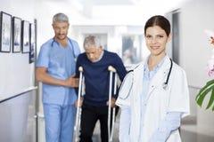 Doktor Smiling While Colleague, das älteren Mann mit Crutche unterstützt lizenzfreies stockfoto