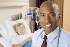 Doktor Smiling, stehend im Krankenhaus-Raum Stockbilder
