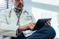 Doktor som använder den digitala minnestavlan i hans kontor Arkivbilder