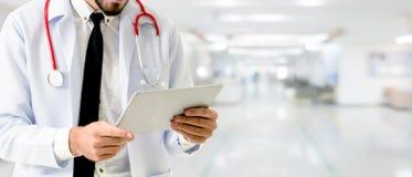 Doktor som använder minnestavladatoren på sjukhuset fotografering för bildbyråer