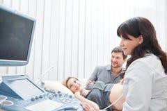 Doktor som använder ultraljudutrustning som diagnostiserar gravida kvinnan arkivfoton