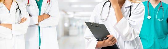 Doktor som arbetar i sjukhus med andra doktorer arkivbild