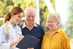 Doktor som arbetar med äldre patienter arkivbild