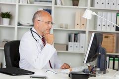 Doktor som arbetar med datoren Arkivfoto