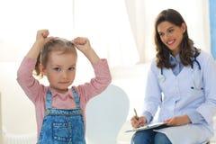 Doktor som arbetar med den lilla patienten i sjukhus royaltyfri bild