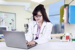Doktor som arbetar på bärbara datorn i sjukhus Arkivbild