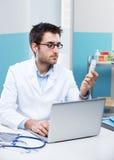 Doktor som arbetar på hans skrivbord Fotografering för Bildbyråer