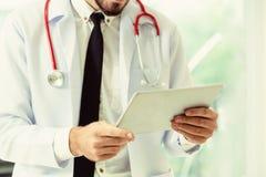 Doktor som arbetar p? minnestavladatoren i sjukhuset arkivfoton