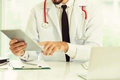 Doktor som arbetar p? minnestavladatoren i sjukhuset arkivbild