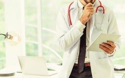 Doktor som arbetar p? minnestavladatoren i sjukhuset fotografering för bildbyråer