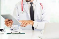Doktor som arbetar p? minnestavladatoren i sjukhuset arkivfoto