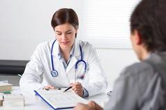 Doktor som ber häftet av en patient fotografering för bildbyråer