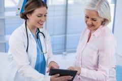 Doktor som diskuterar med patienten över den digitala minnestavlan Arkivbilder