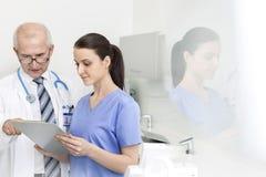 Doktor som diskuterar med sjuksköterskan över skrivplattan på den tand- kliniken arkivbild