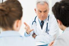 Doktor som diskuterar med tålmodig Arkivfoto