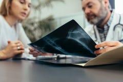 Doktor som diskuterar medicinska bildläsningsresultat med patienten royaltyfria foton