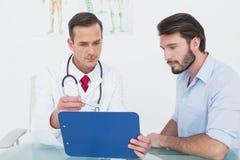 Doktor som diskuterar rapporter med patienten på det medicinska kontoret Arkivfoton