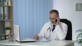 Doktor som diskuterar resultat av patientprov som gör rekommendationer vid telefonen lager videofilmer