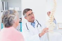Doktor som explaning den anatomiska ryggen till den höga kvinnan fotografering för bildbyråer