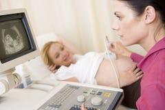 doktor som får den gravida ultrasoundkvinnan Arkivfoto