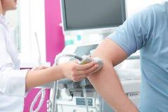 Doktor som för ultraljudundersökning av armbågeskarven i klinik arkivfoton