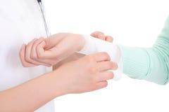 Doktor som förbinder den kvinnliga handen över vit Royaltyfri Foto