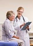 Doktor som förklarar det medicinska diagrammet till den höga kvinnan fotografering för bildbyråer