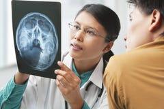 doktor som förklarar det patient skelett till röntgenstrålen Royaltyfri Fotografi