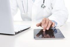 Doktor som fungerar på en digital tablet arkivfoton