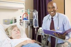 doktor som gör anmärkningspensionärkvinnan royaltyfria bilder