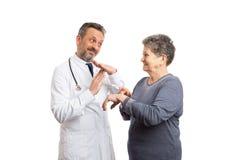 Doktor som gör denTime gesten medan tålmodiga punkter på handleden arkivbild