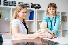 Doktor som ger en gåva till en flicka Arkivbild