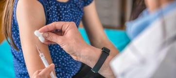 Doktor som ger en ung flicka ett vaccinskott arkivfoton